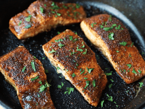 overhead view of a cast iron skillet containing blackened salmon
