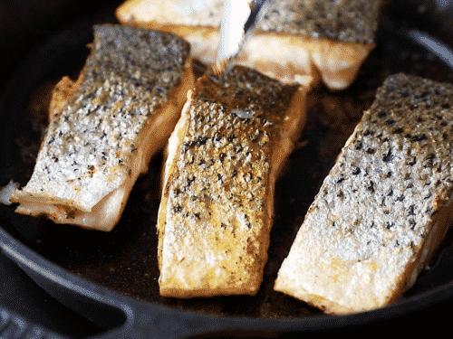 close up of crispy skin salmon inside of a cast iron skillet