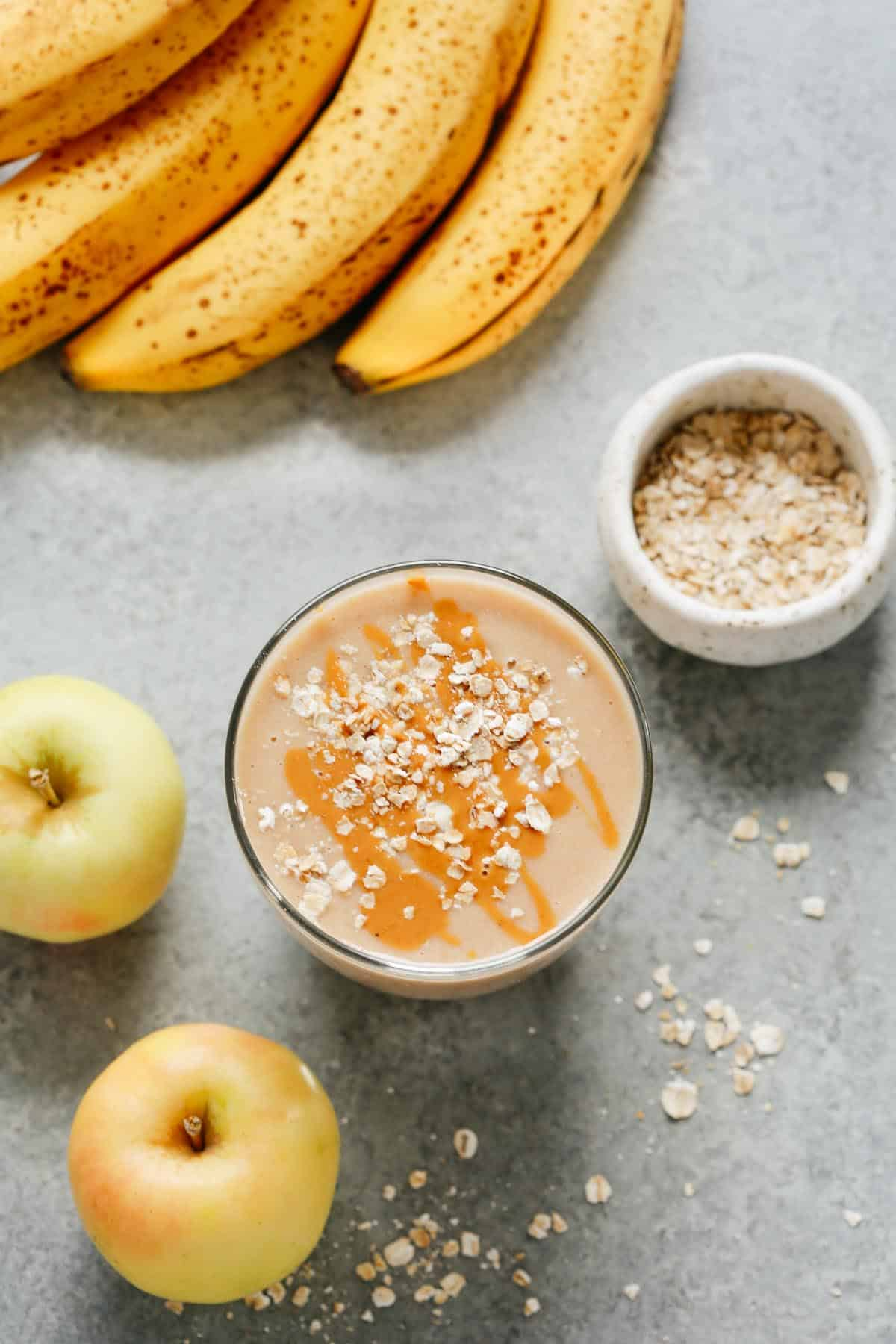 cup of apple smoothie with oats sprinkled on top with bananas, apples, and oats placed beside it