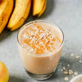 cup of apple smoothie with oats sprinkled on top