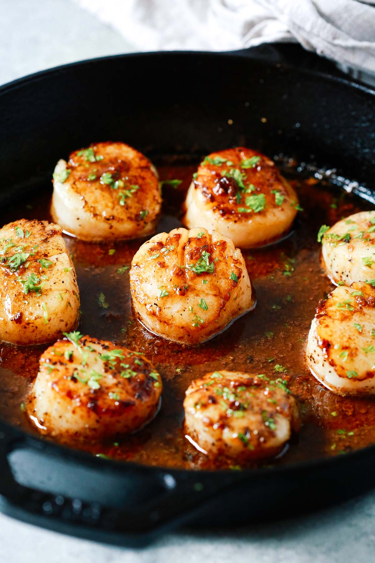 golden pan seared garlic butter scallops in a cast iron