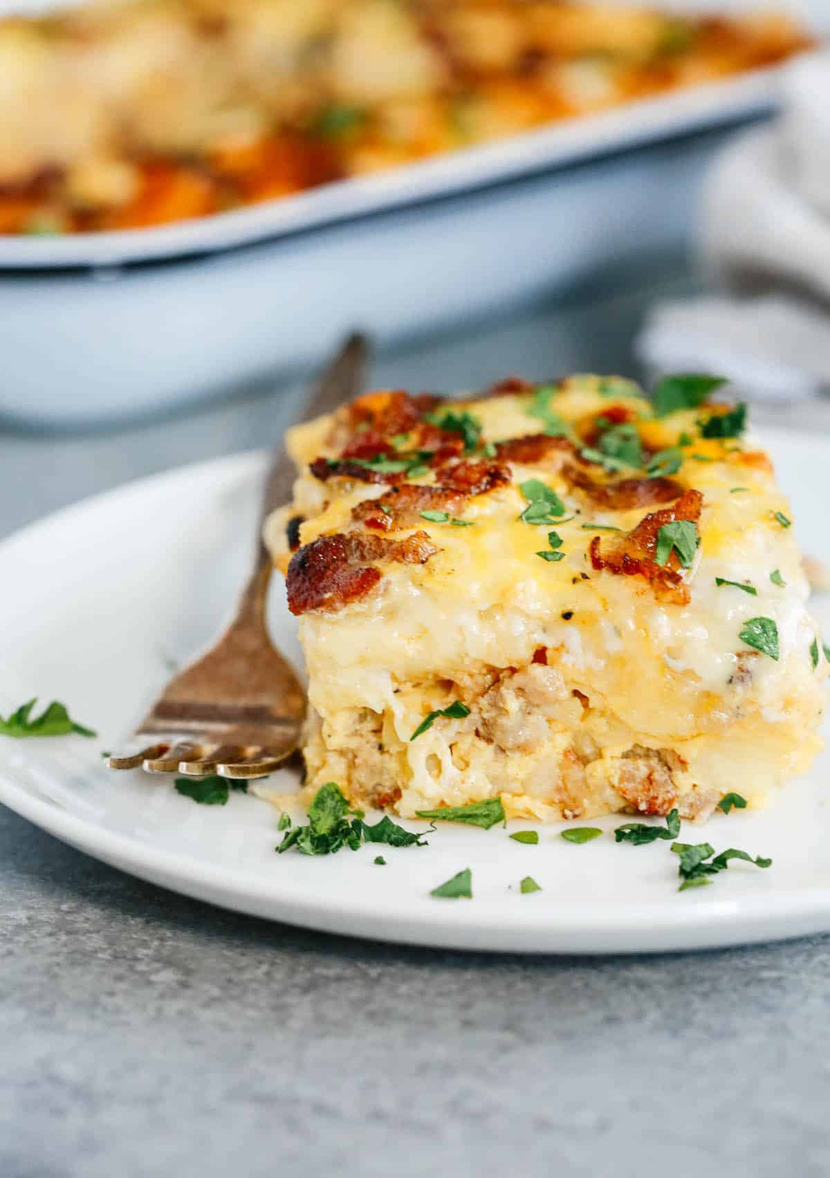 a slice of Sausage and Potato Breakfast Casserole on a plate with a fork