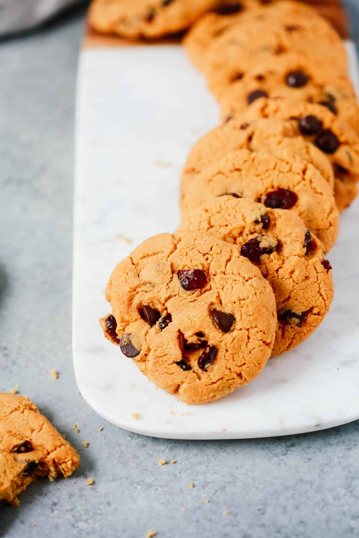A row of chocolate chip cookies with cranberries in a row on a marble serving board.
