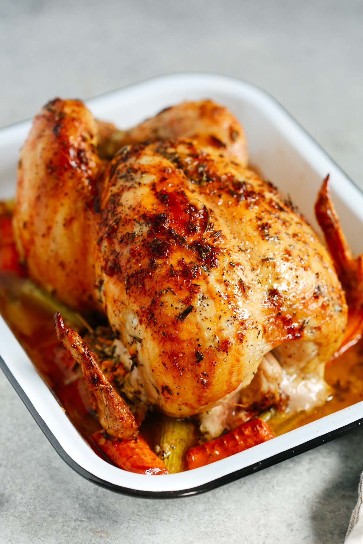 Photo of a garlic herb butter roast chicken inside of a white roasting pan.