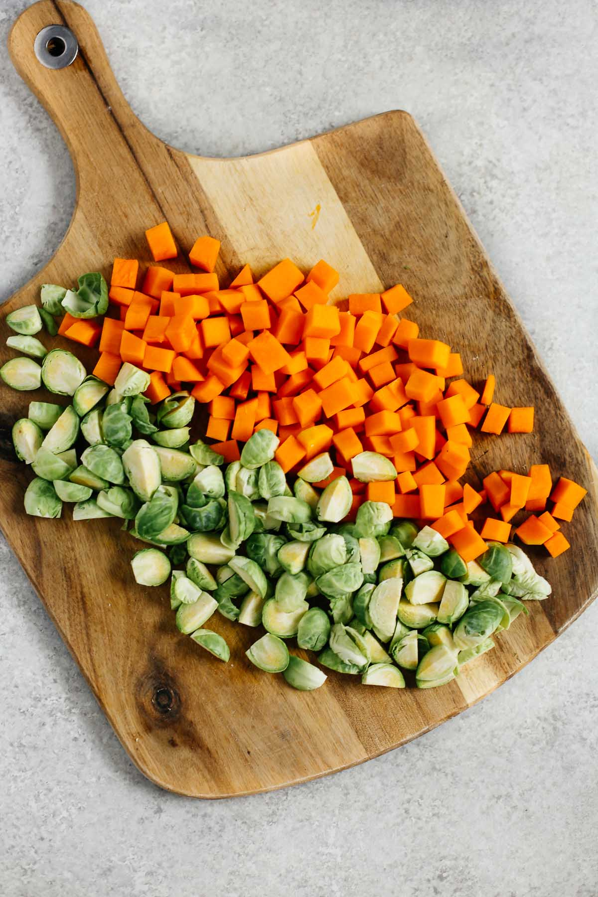 Overhead image of a cutting board with diced butternut squash and quartered Brussels sprouts.