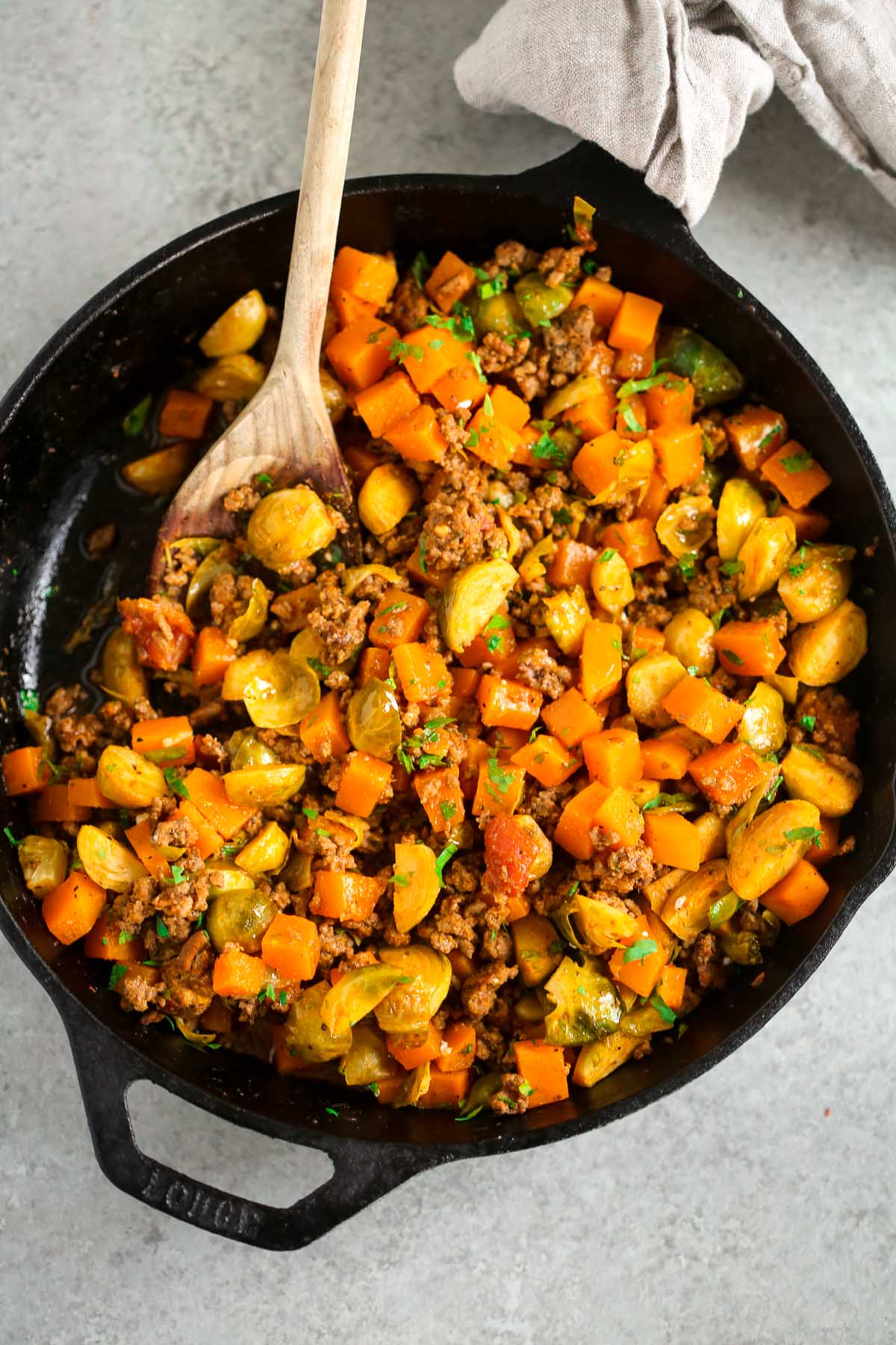 A cast iron skillet with ground beef with butternut squash with a wooden spoon scooping.