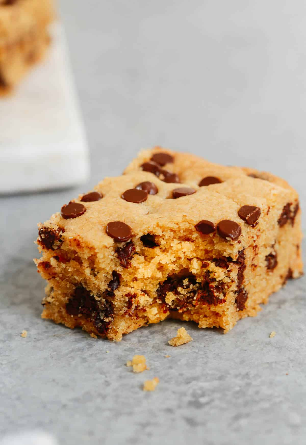 Close up of a cookie bar with a bite taken out of it.