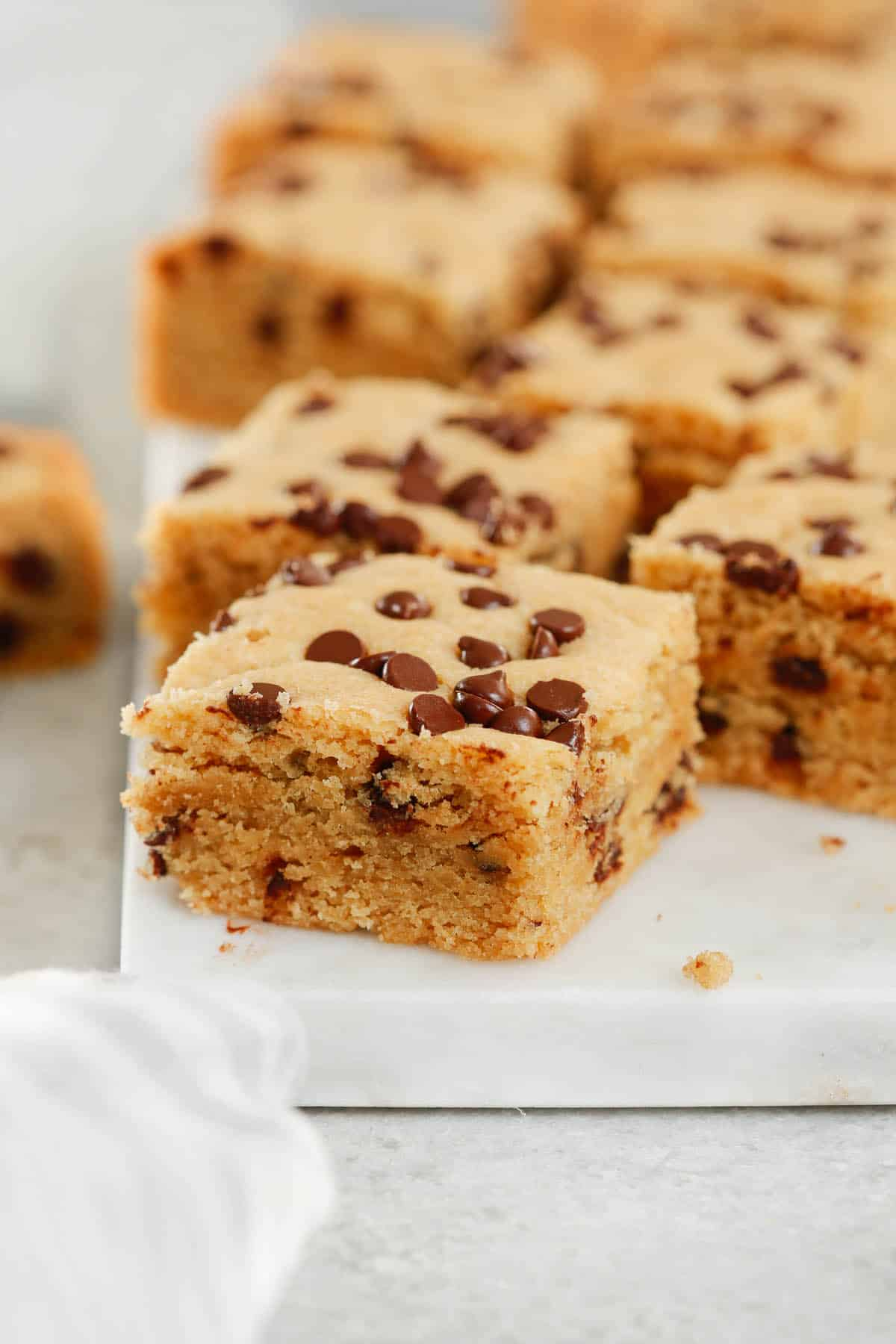 Close up of healthier chocolate chip cookie bars on a marble serving board.