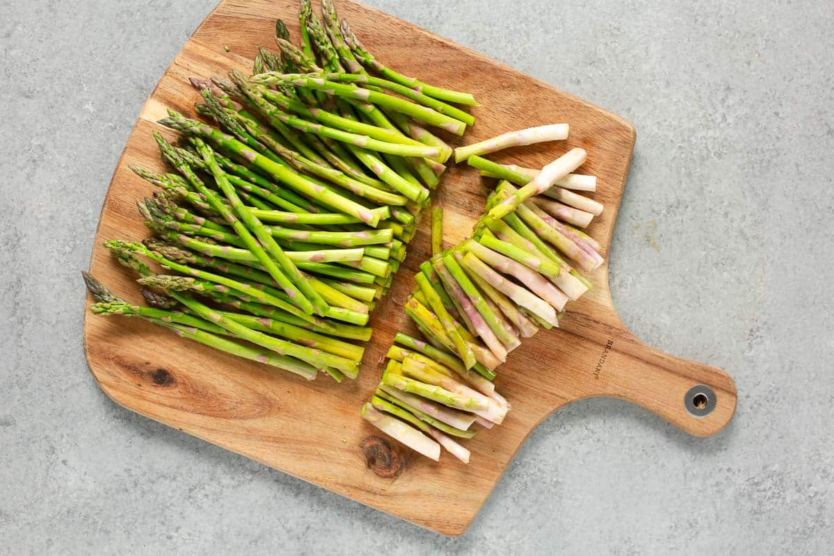 Cutting off the woody ends of asparagus spears on a cutting board.