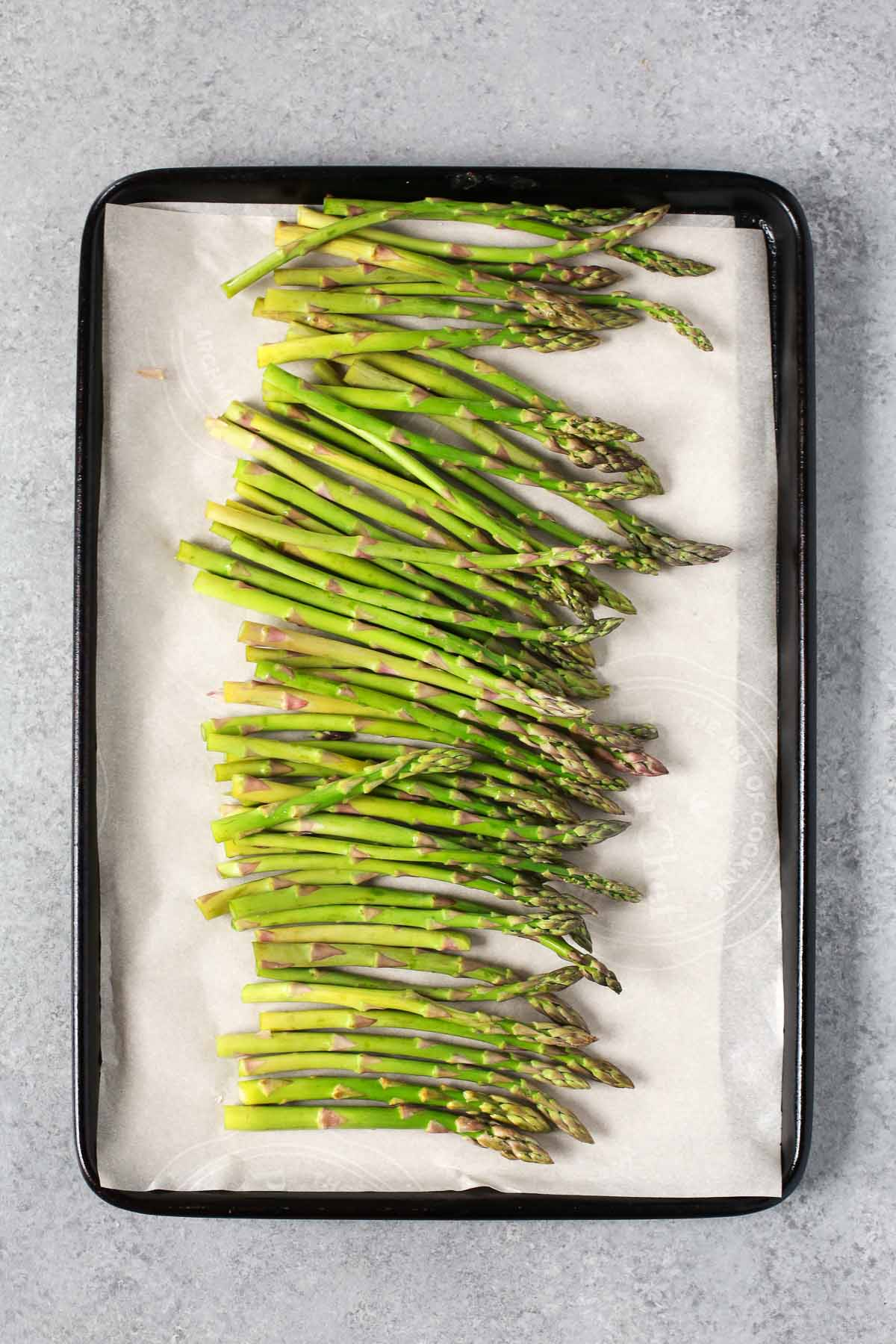 Placing prepared asparagus onto a sheet pan lined with parchment paper.