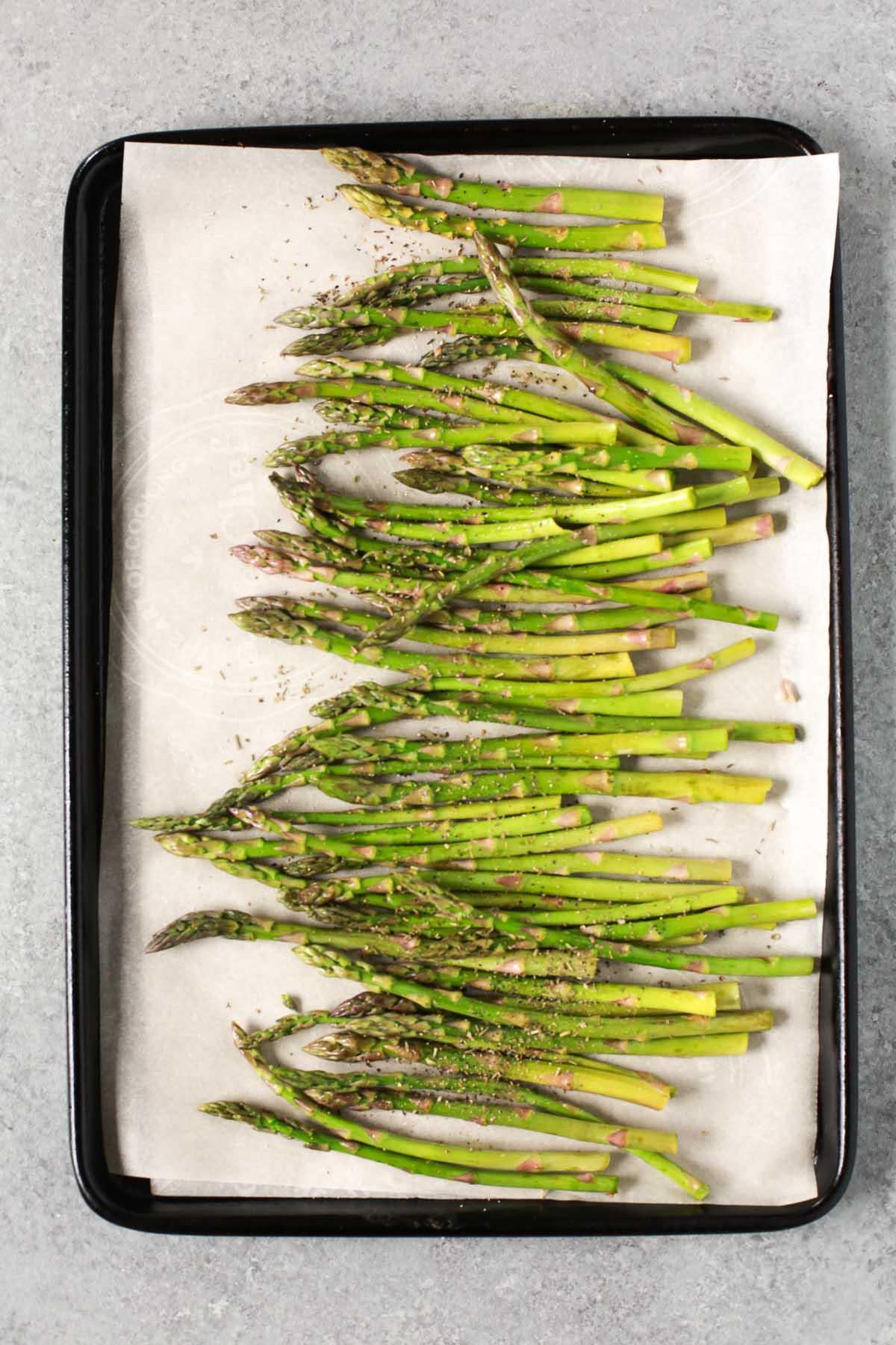 Seasoning asparagus on a sheet pan before roasting.