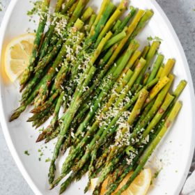 Easy roasted asparagus on a serving platter topped with parmesan cheese and lemon wedges.