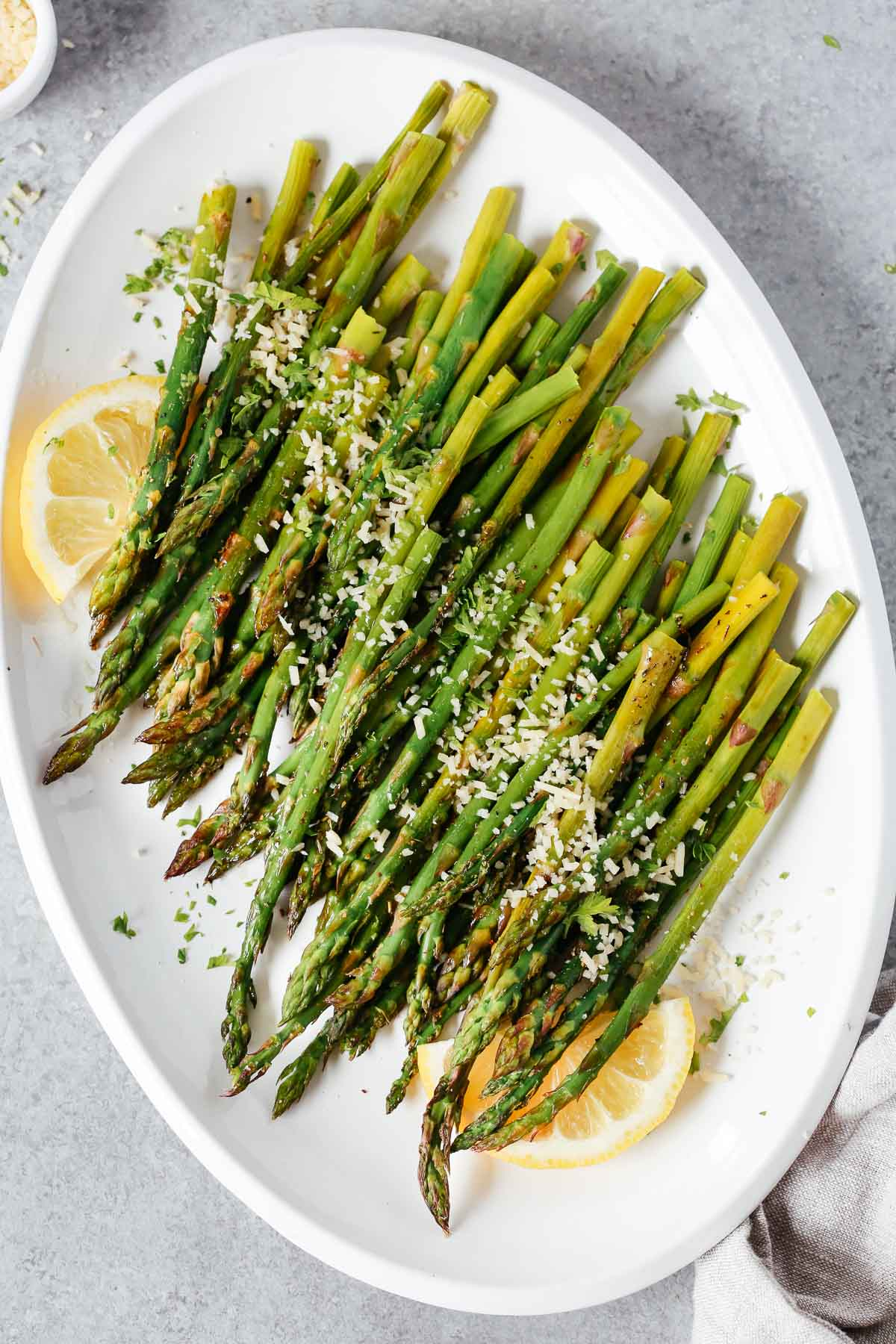 Roasted asparagus on a serving platter topped with parmesan cheese and lemon wedges.