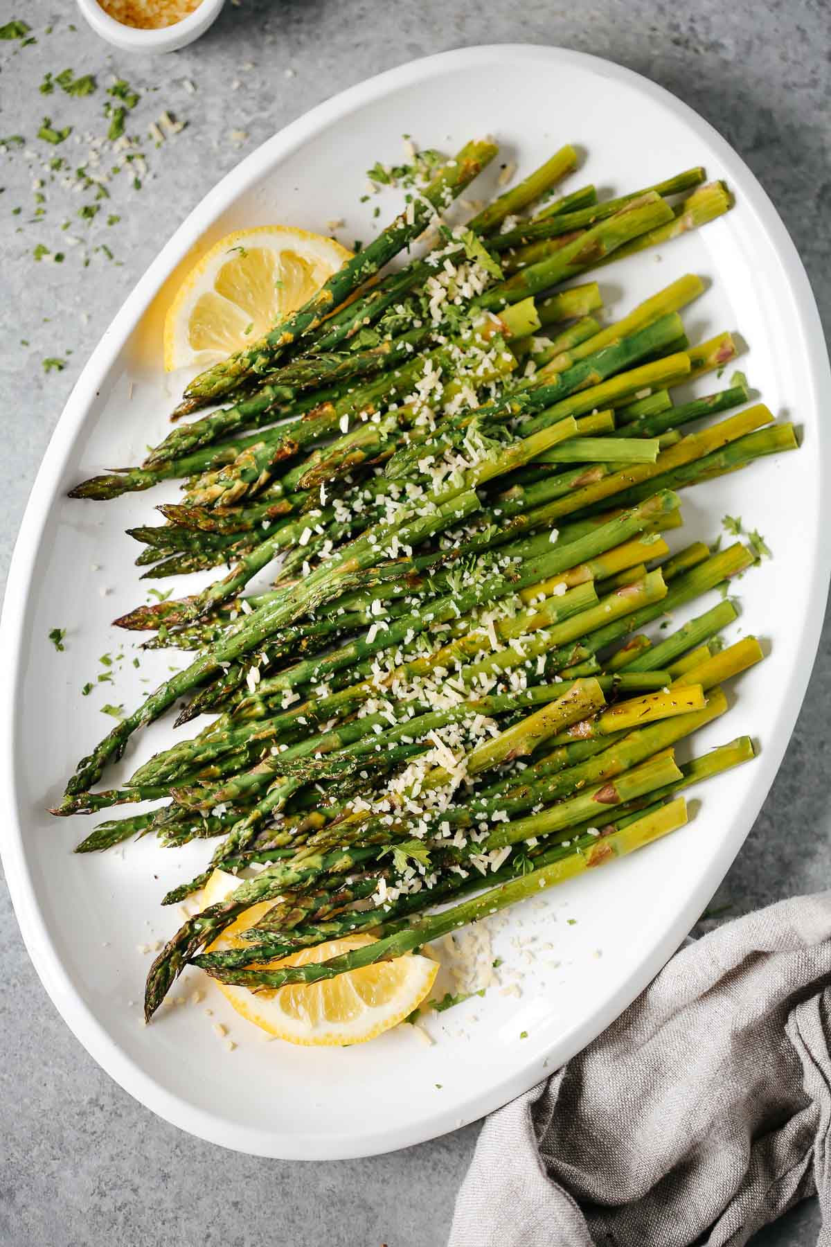 Easy roasted asparagus on a white plate topped with parmesan cheese and lemon wedges.