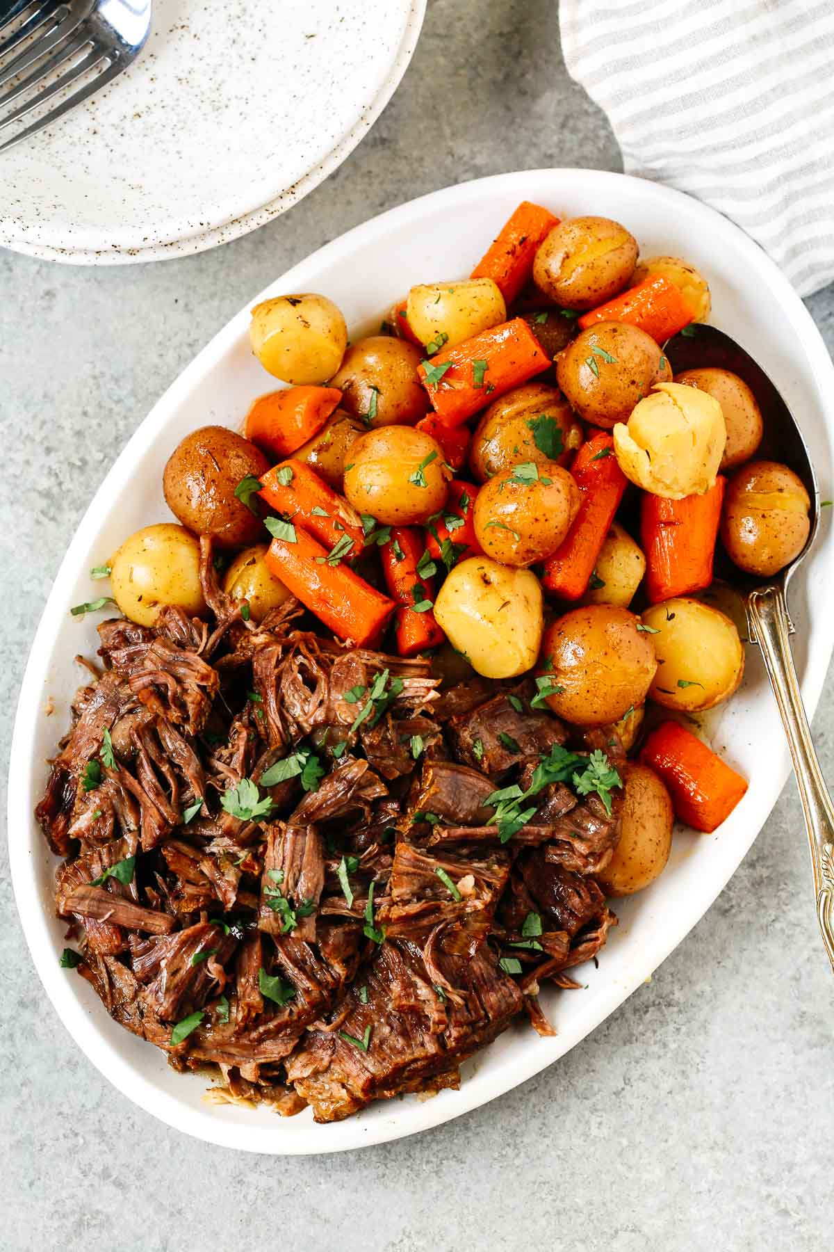 White serving plate containing Instant Pot pot roast and potatoes and carrots.