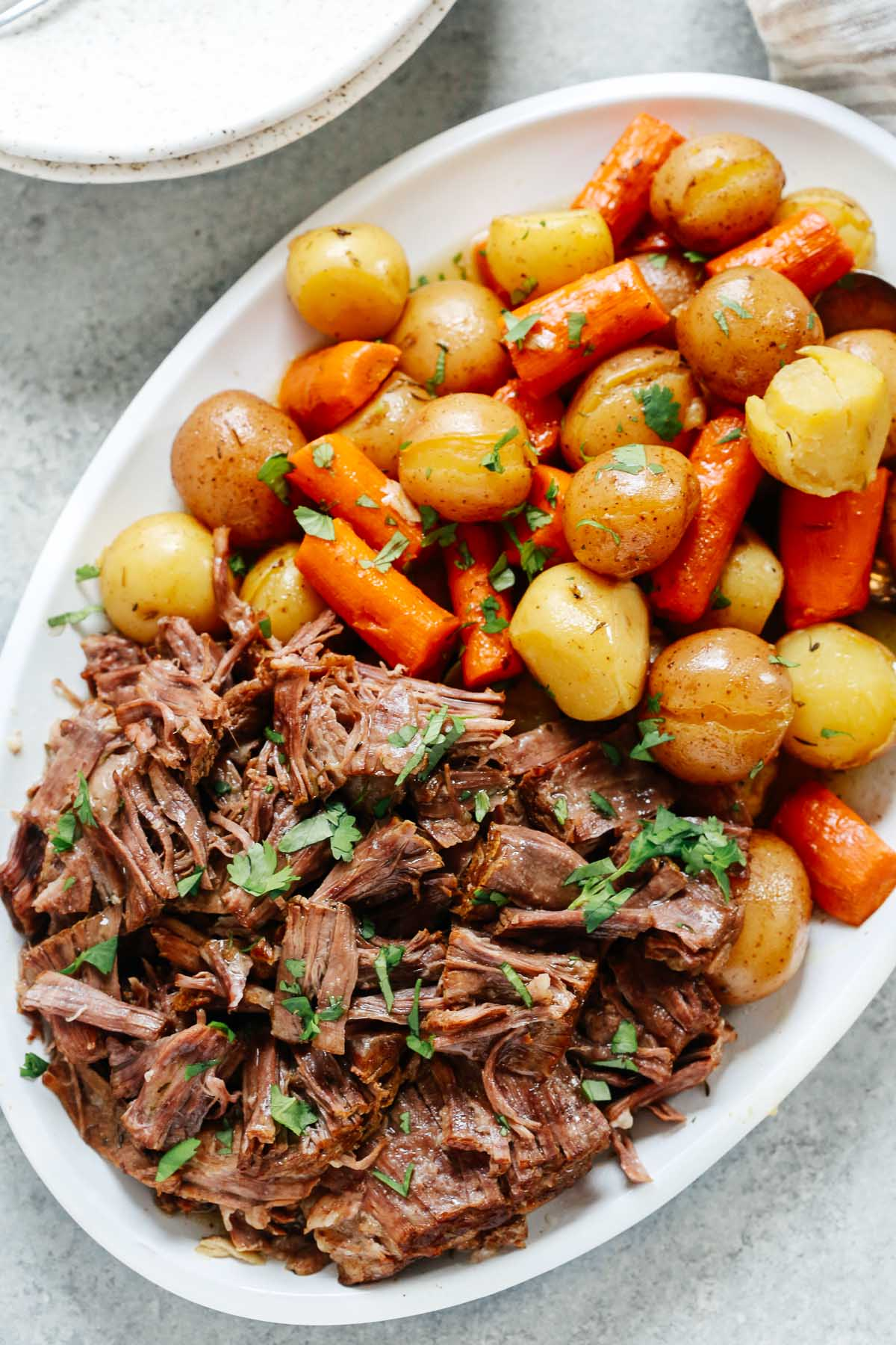 Pressure cooker pot roast recipe in a white serving plate with carrots and potatoes.