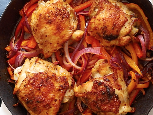 Overhead view of cast iron skillet containing chicken thighs, slices of onions and bell pepper