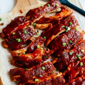 A close up of a baked ribs on a wooden cutting board
