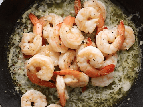 overhead view of a cast iron skillet containing shrimp