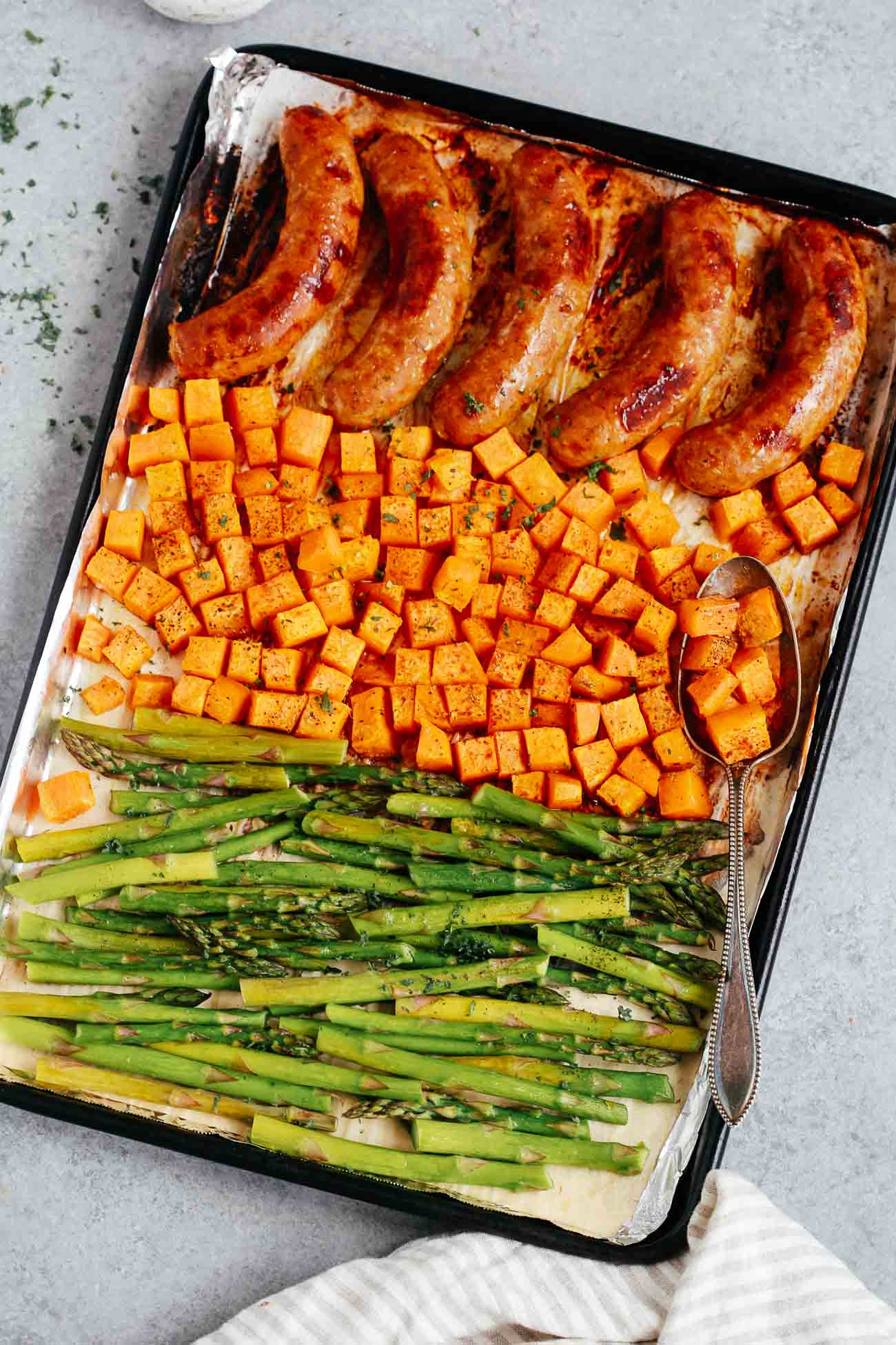 Overhead view of a sheet pan containing cooked sausage, sweet potatoes, and asparagus.