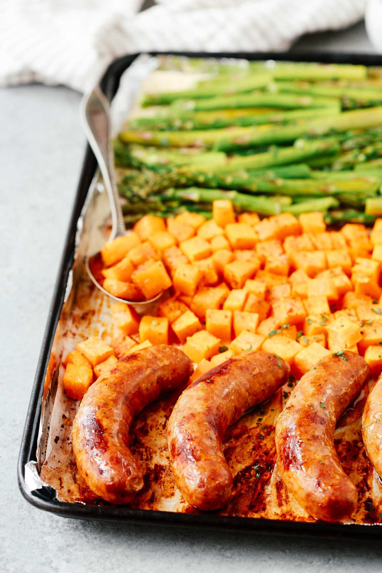 Sheet pan with sausage, sweet potatoes, and asparagus.