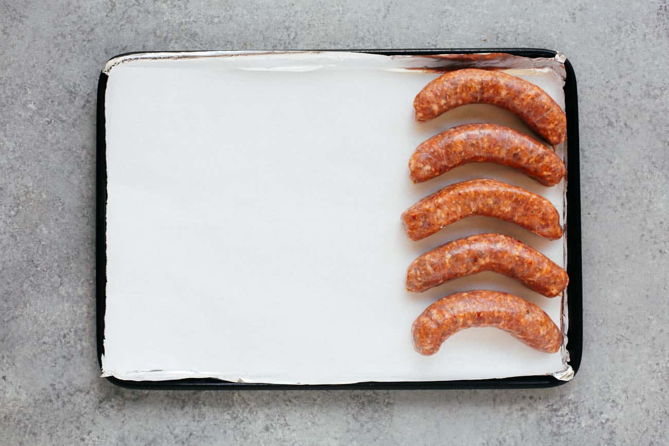 A sheet pan with five sausages.