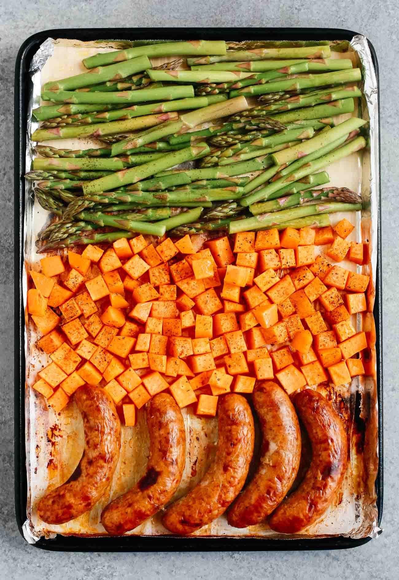 A sheet pan with sausage, potatoes, and asparagus.