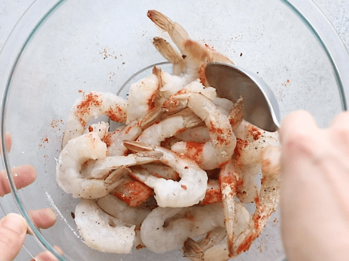 overhead view of a large glass bowl containing shrimp and spices