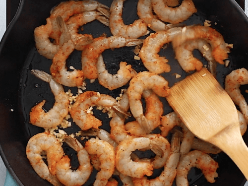 overhead view of cast iron skillet containing shrimp and sausage