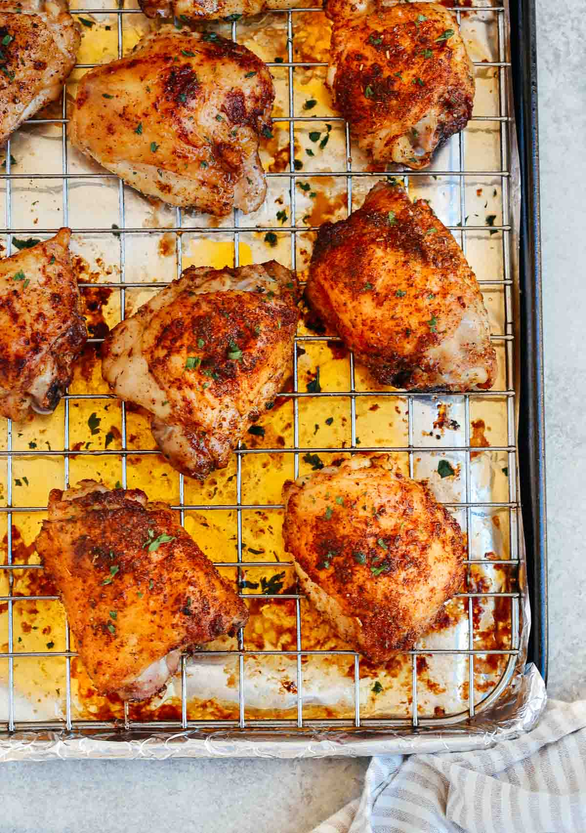 Easy baked chicken thighs cooling on a rack over a sheet pan.
