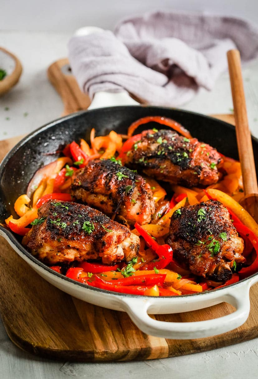 close up of a white skillet containing Chicken and Peppers