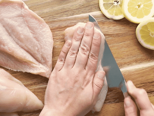 chicken breast on a cutting board. The chicken breast is cut horizontally into two even pieces