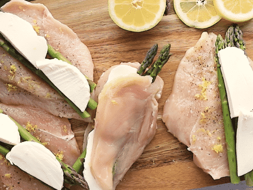overhead view of asparagus stuffed chicken breast on top of a cutting board