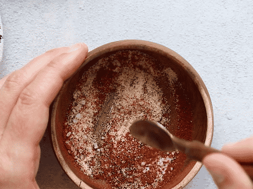 overhead view of a small wooden bowl containing spices