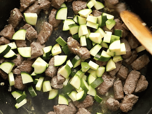 overhead view of a cast iron skillet with diced beef and zucchini