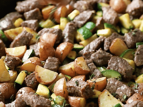 closeup of diced potatoes, beef and zucchini in a cast iron skillet