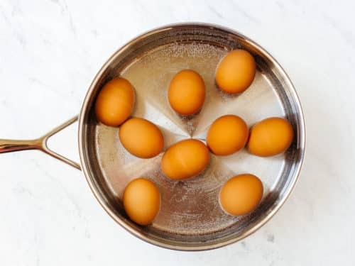 overview of a pan filled with water and 9 eggs inside to be boiled