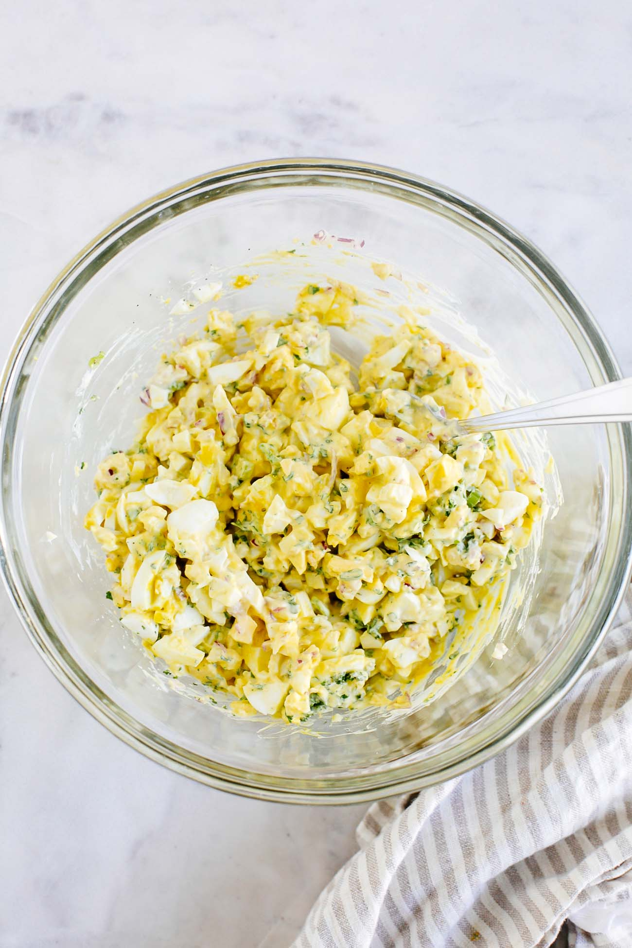 Egg salad being mixed in a bowl.