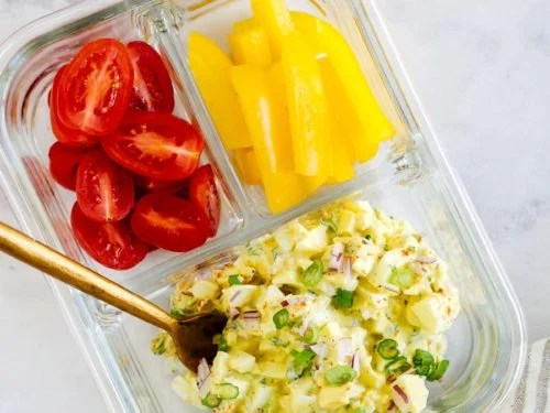 overhead view of a glass container with cherry tomatoes, bell pepper and egg salad
