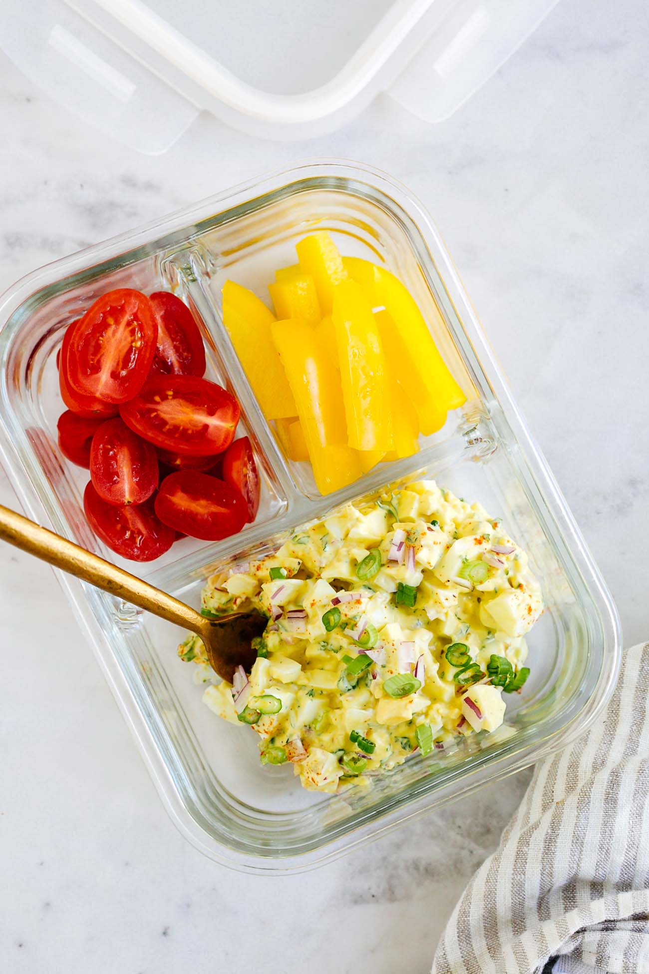 Meal prep container with 3 compartments holding egg salad, cherry tomatoes, and bell peppers.