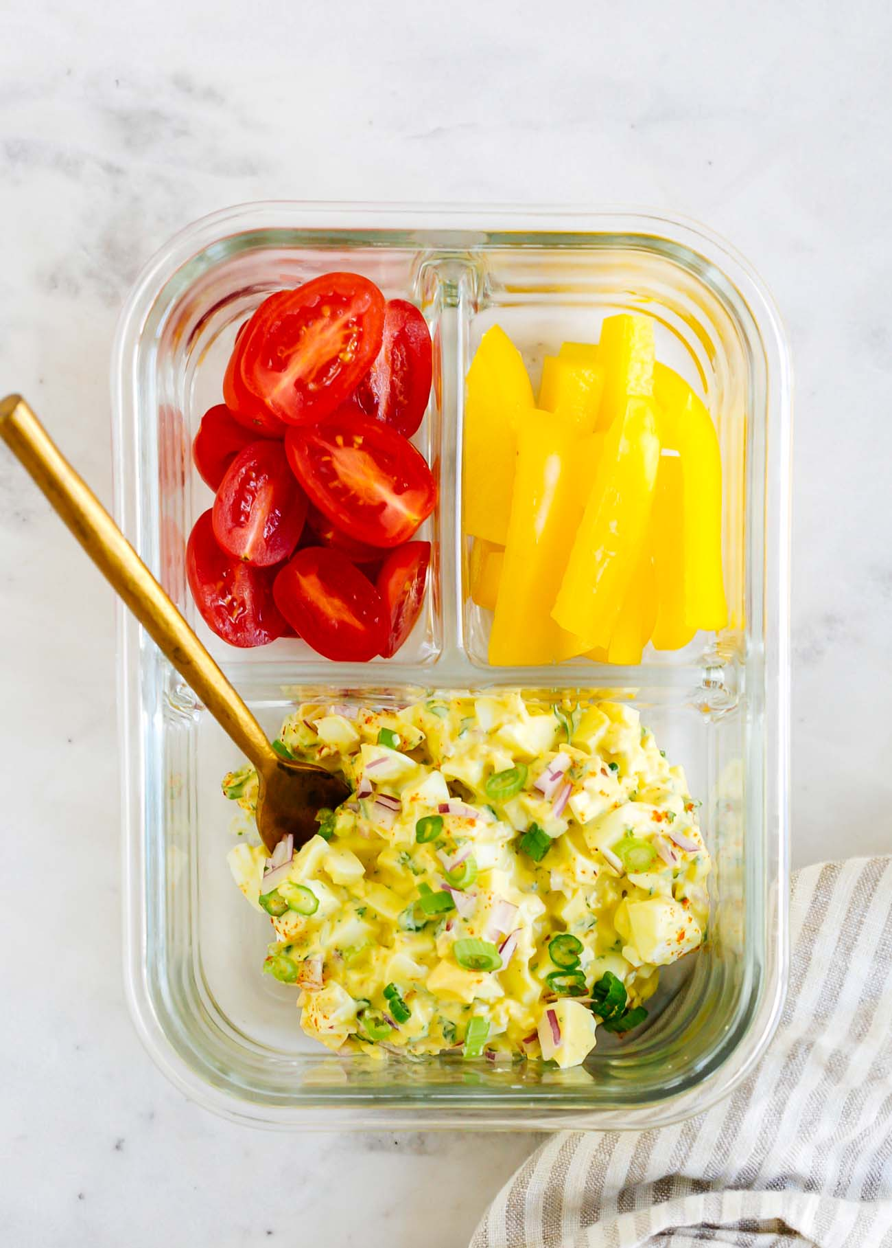 Meal prep container with egg salad, cherry tomatoes, and bell peppers.