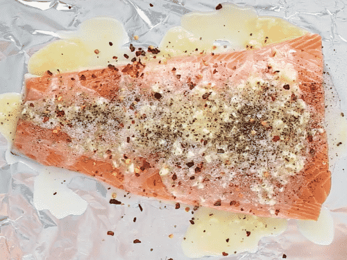 overhead view of salmon with melted butter in a baking sheet