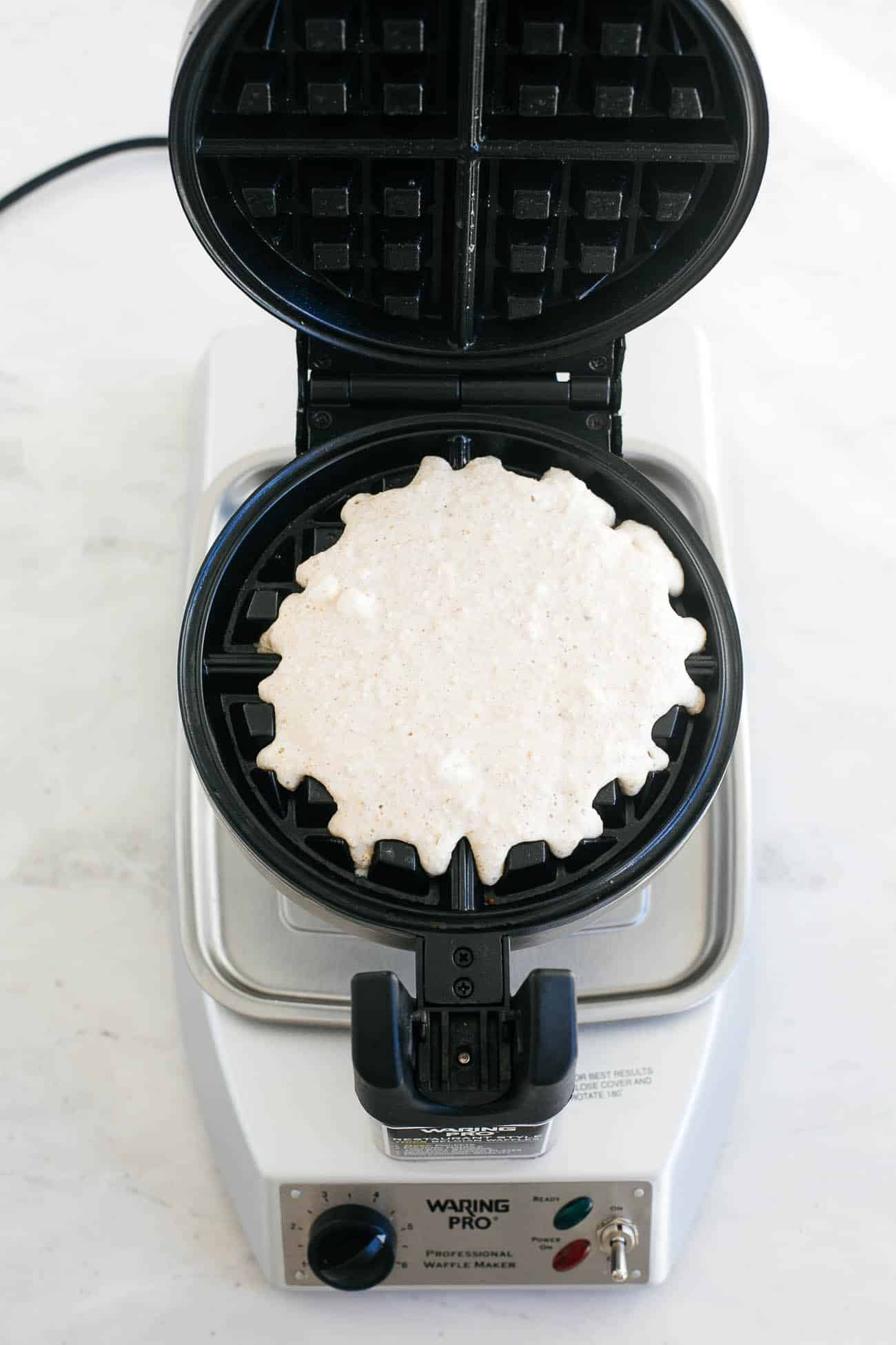 Batter going into a waffle maker.