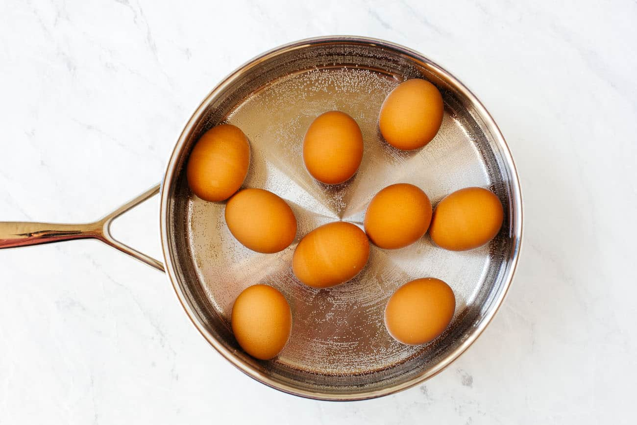 Eggs inside of a pot of water to be boiled.