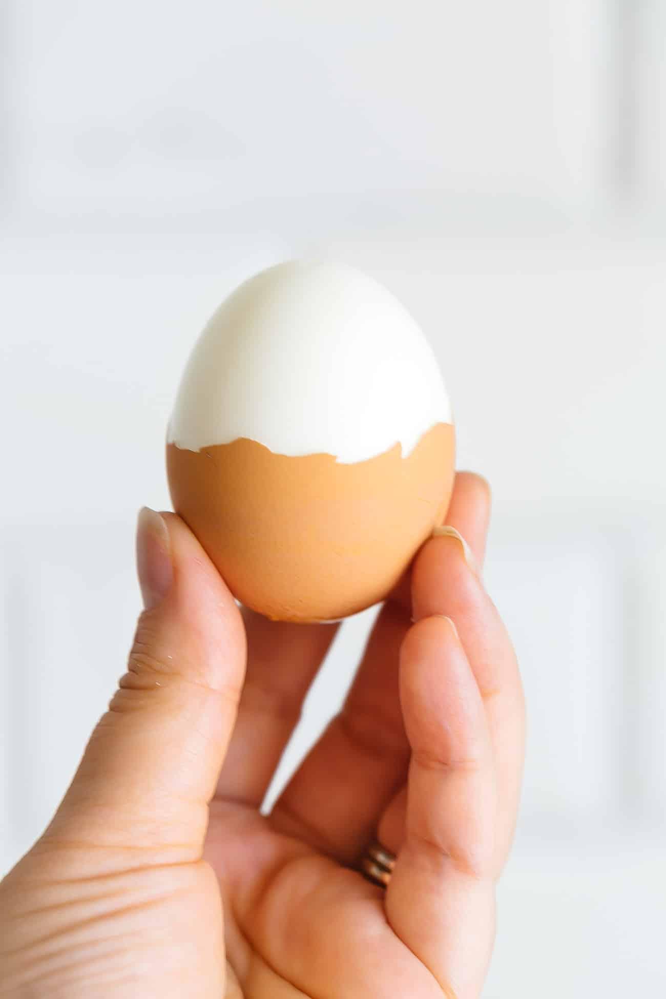 A hand holding a half peeled hard boiled egg.