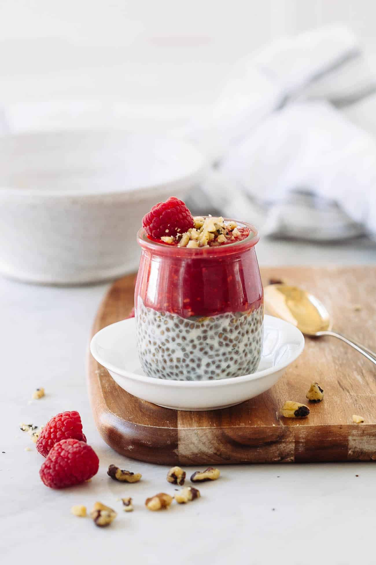 A jar of chia seed pudding with raspberry puree, raspberry, and pistachios on top.
