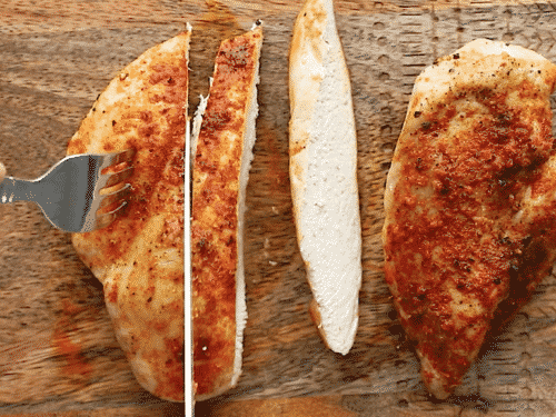overhead view of a baked chicken in a wooden cutting board