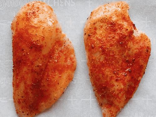 overhead view of seasoned raw chicken breast on a baking sheet