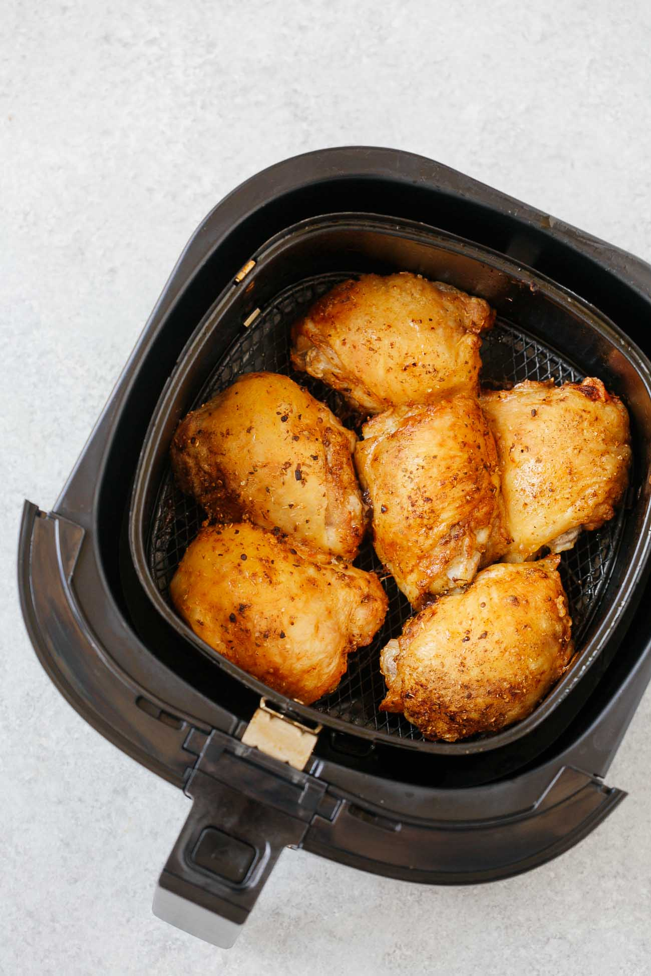 overhead view of cooked chicken thighs inside of an air fryer basket.