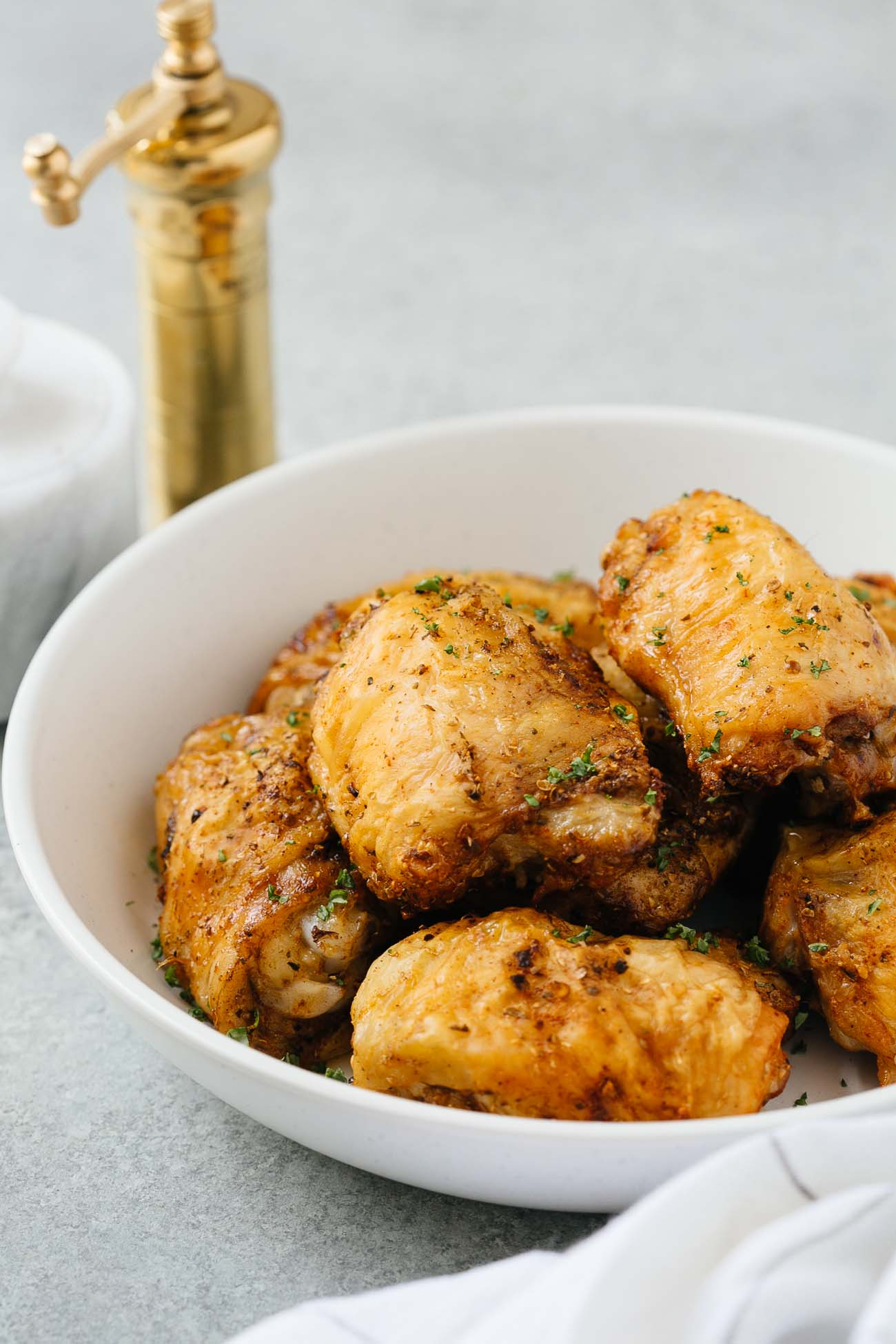 A white bowl with air fryer chicken thighs.